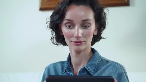 junge brünette Frau, die mit Tablet arbeitet, sitzt zu Hause auf dem Sofa. Volles Gesicht. hd