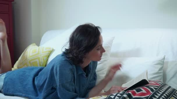 Volný čas. Mladá bruneta žena čte knihu vleže na pohovce. Profil. HD