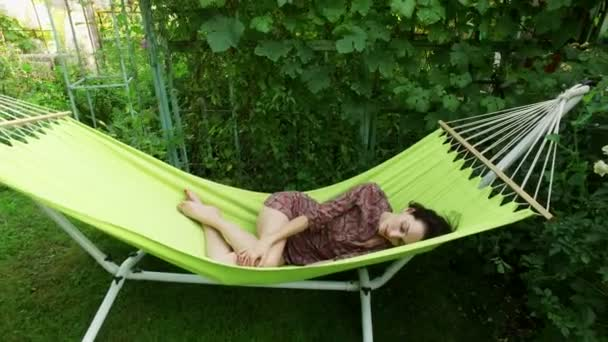 Garden. A young dark-haired woman resting in a hammock. Afternoon sleep. 4K