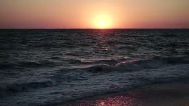 Přímořská krajina. Západ slunce. Mořské vlny válcování na písečnou pláž v paprscích zapadajícího slunce. Široký úhel. HD