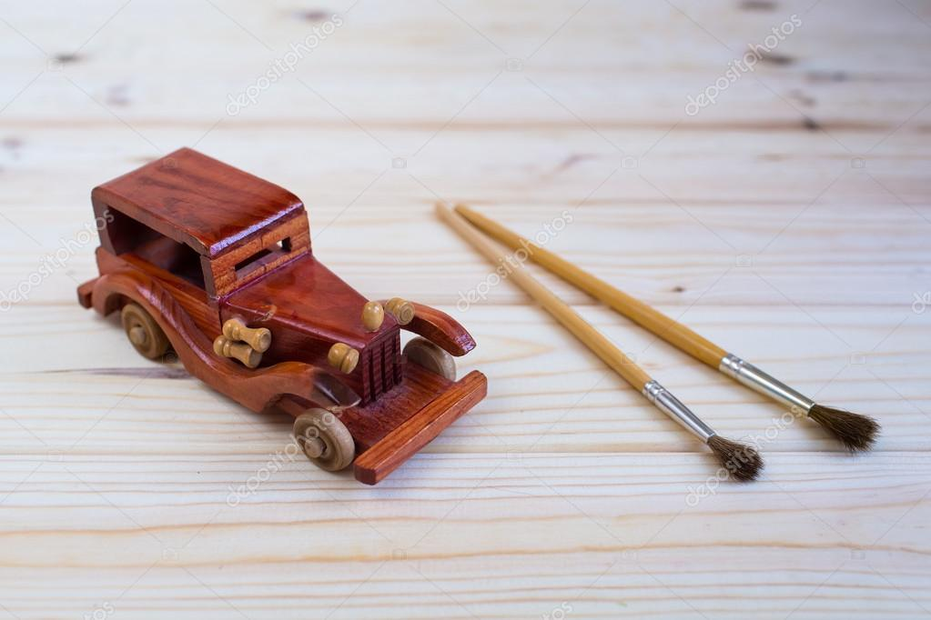 Wooden Toy Car And A Brush To Paint On The Wooden Background