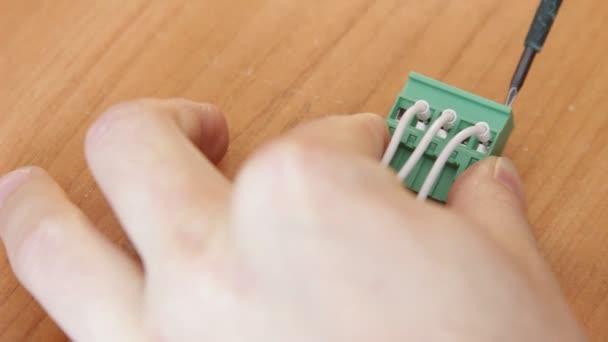 Primo piano di operaio elettricista avvitamento dei fili.