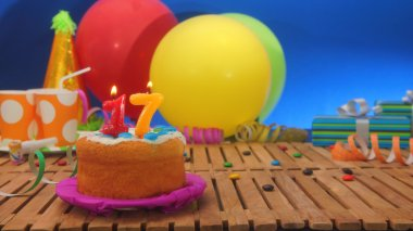 Birthday cake with candles on rustic wooden table with background of colorful balloons, gifts, plastic cups and candies with blue wall in the background