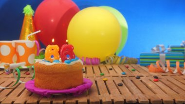 Birthday cake with candles on rustic wooden table with background of colorful balloons, gifts, plastic cups and candies with blue wall in the background.