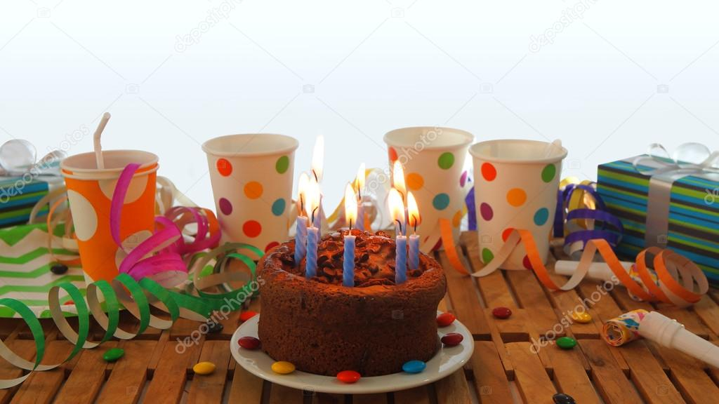 Chocolate Birthday Cake With A Blue Candles Burning On Rustic Wooden Table Background Of Colorful Streamers Gifts Plastic Cups Candies And White