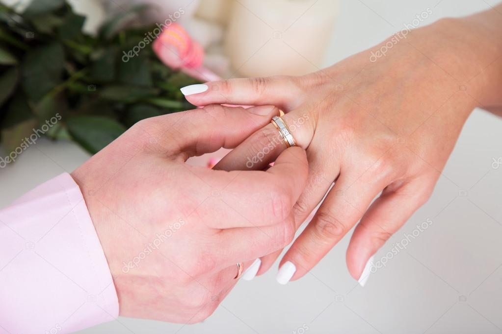 bb5209f3c6d4 Las manos con anillos novio poniendo el anillo de oro en el dedo de la novia  durante la ceremonia de boda primer plano par de amar.