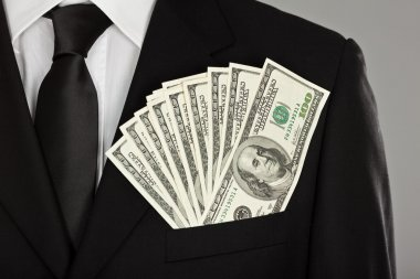 satisfied and happy businessman keep dollar money in pocket suit