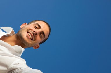 handsome young man opens a box outdoor with blue sky