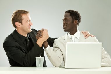 black and white businessman interracial teamwork with laptop isolated on grey