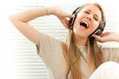 Giovane bella donna ascolta musica con la cuffia in un salotto