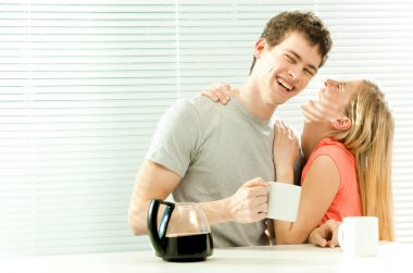 Young casual couple have breakfast with coffee with venetian blind window