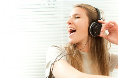 Young beautiful woman listen music with headphone in a living room