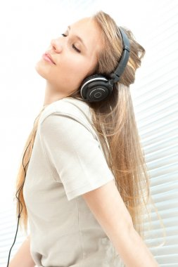 Young beautiful woman listen music with headphone in a living room stock vector