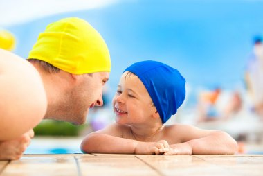 Happy child and dad with swimming pool cap have fun in a pool