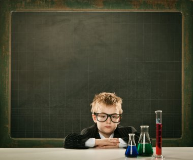 young elegant clever chemistry student or scientist serious pose with blackboard