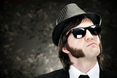 elegant boss man with sideburns and sunglasses on black backround