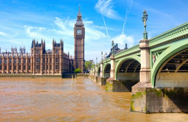 London westminster houses of parliament and bridge on river thames in a sunny day
