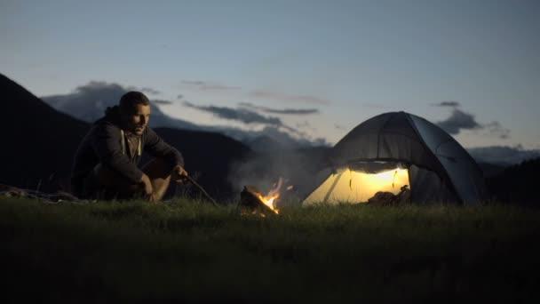Mladý muž oteplování s táborového ohně v přírodě horský venkovní táboření scéně