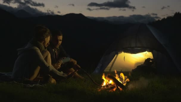 Group of three friends warming with camp fire in nature mountain outdoor
