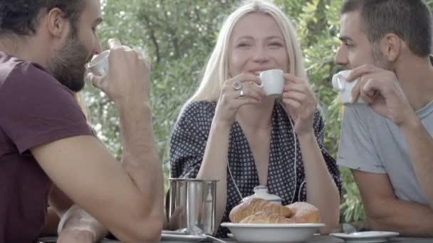 Skupina čtyř happy přátel, muži a ženy úsměv, smích a pít kávu