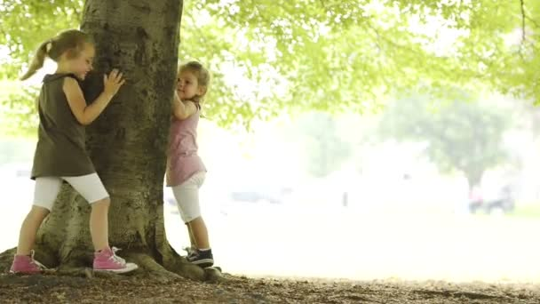 Happy blonde sisters are playing outdoor hide and seek at town park