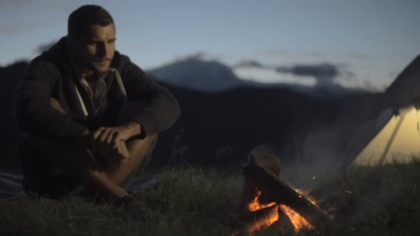 Young man warming with camp fire in nature mountain outdoor