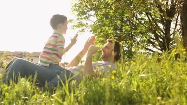 Father and son in summer day are playing lying down on the grass