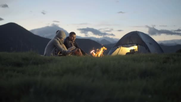 Group of three friends warming with camp fire in nature mountain