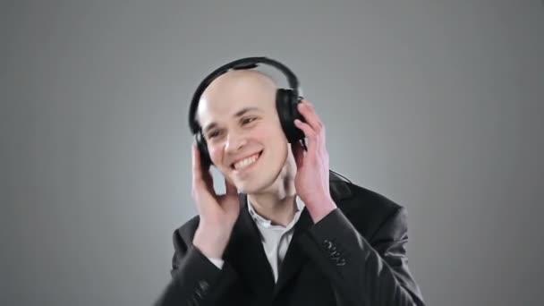 Elegáns kopasz fiatalember a hallgató zene