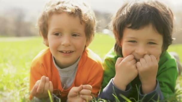 Children laying down on grass and making faces