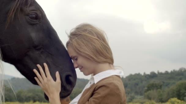 Mladá žena usměje objetí a polibky černém koni
