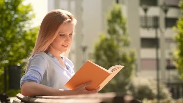 Young beautiful blonde girl in summer day is reading a book