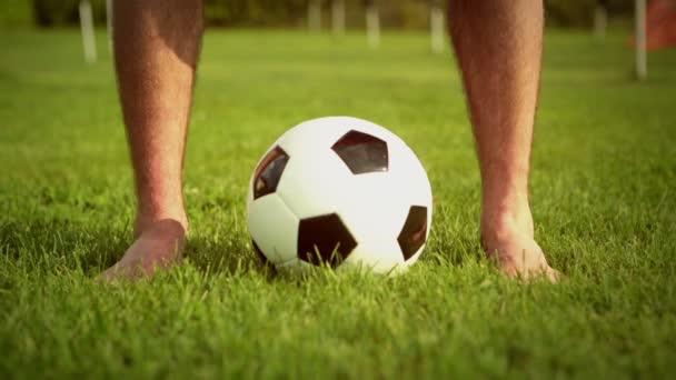 Fiatal férfi szabadtéri hit a labdát a csupasz lábak