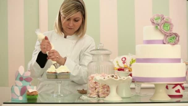Giovane pasticcere è guarnire torte della tazza