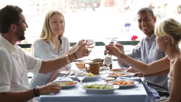 Four multiethnic friends are eating at italian restaurant