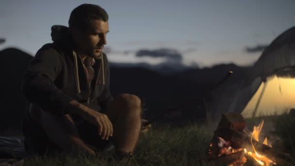 Mladý muž oteplování s táborového ohně v přírodě horské venkovní