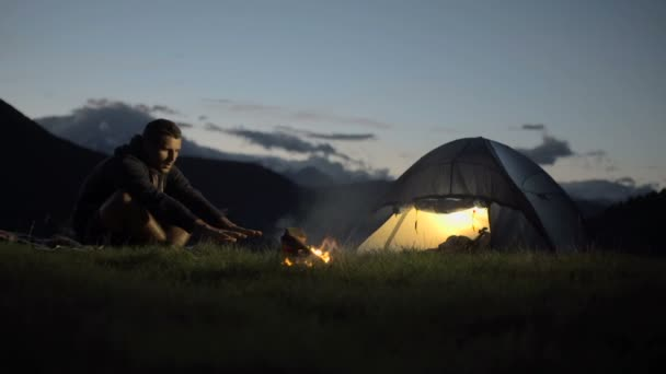 Young man warming with camp fire in nature mountain outdoor camping scene
