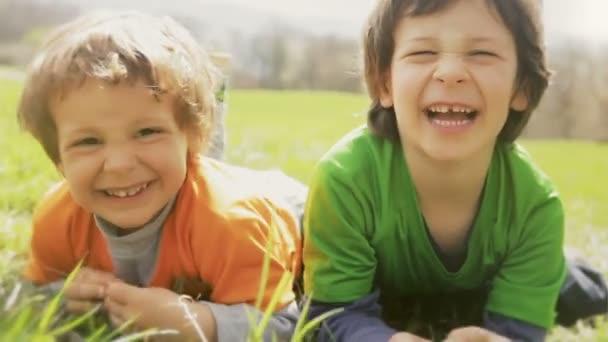 Kinder legen sich auf Gras und machen Gesichter