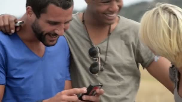 Four multiethnic friends in summer day with smarphone having fun