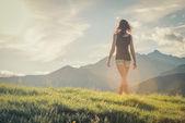 Retro giovane donna a piedi sulla montagna in giorno pieno di sole