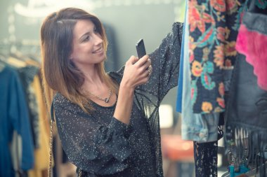 Young brunette woman choose clothes in shop