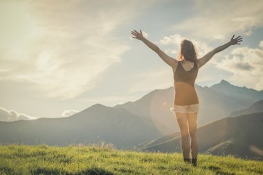 Young backside woman walk on mountain in sunny day