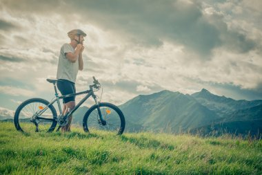 Young man stand near bike on mountain outdoor