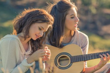 Genç kadın şarkı gitar çalmak arkadaşıyla günbatımı açık
