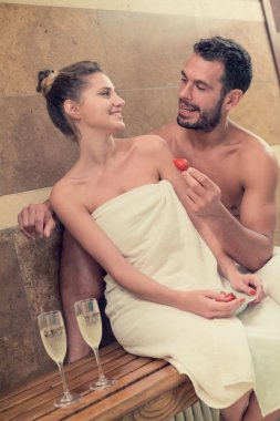 Young smiling couple relaxing in bath tub with strawberry and champagne at spa