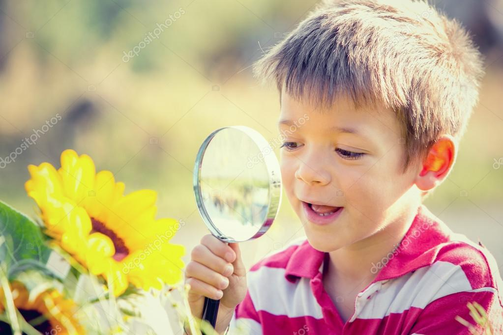 smiling child playing with magnifying glass in a garden
