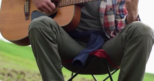 Detailní záběr muže ruce hrát na kytaru během kempování