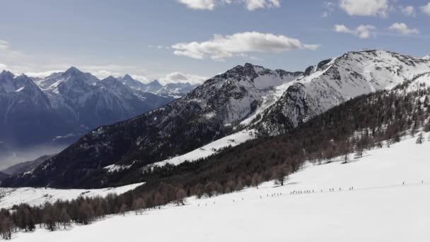 zimní vzduch nad skupinou lidí se sněžnicemi, kteří se procházejí po zasněženém svahu. Zimní říše divů panorama s aktivními lidmi.Hory venkovní zřizovatel.4k drone vpřed let