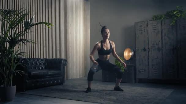 Frau beim Kniebeugen zu Hause. Gesunde Frau in Sportkleidung, die zu Hause Kniebeugen macht. Frau beim Training im Wohnzimmer. Zeitlupe