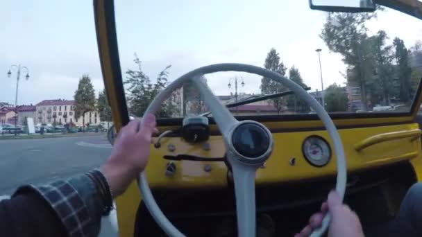 Muž řídí své žluté auto v opuštěném městě. Na straně charakteristické domy, dlážděná ulice a borovice